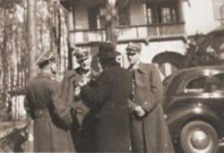 Ks. Leon Bemke (tyłem, w kapeluszu) z polskimi oficerami na Westerplatte. Ze zbiorów Andrzeja Drzycimskiego.